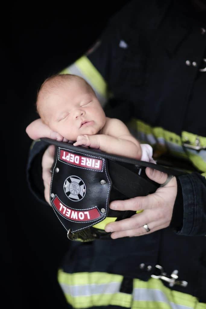 newborn girl in sleeping in firefighters hat