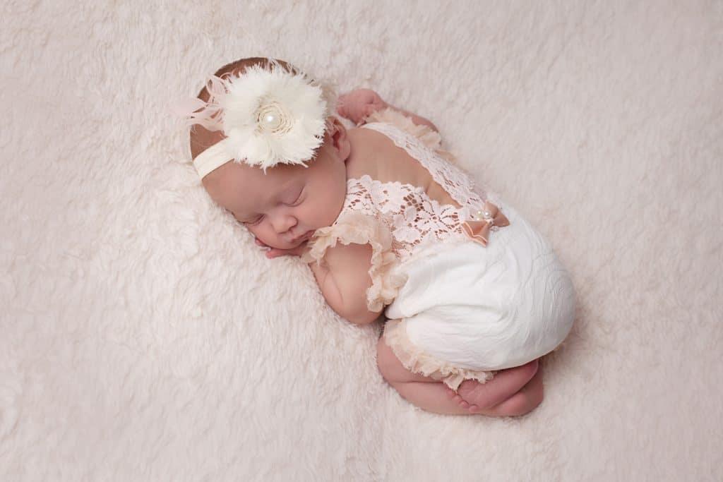 newborn on tummy in lace romper